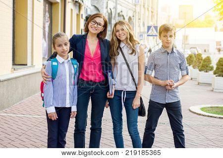 Portrait of female teacher with children standing outside school