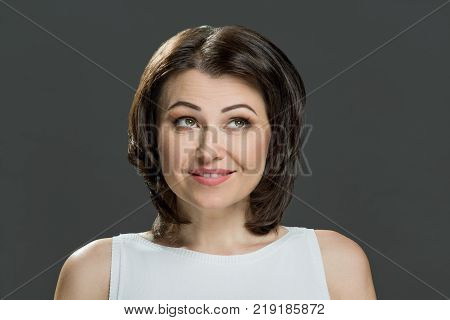 Portrait of emotional beautiful mid adult woman on grey background