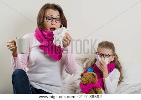 Sick mother and daughter. A woman with a runny nose, she sneezes, using a handkerchief, drinking hot tea, medicine.