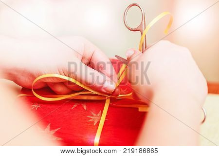 Creative diy craft hobby. Making handmade craft ribbon with scissors. Female hands with scissors and red gift box close up. Selective focus umage. Christmas or New Year concept
