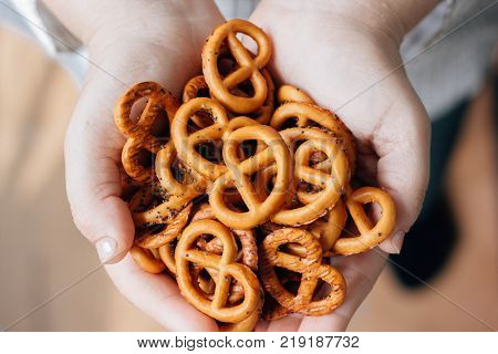 Woman holding hip of pretzel or bretzel in hands.