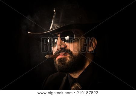 Portrait of elegant man in suit with black cowboy hat is smoking cigar on black background. Clint Eastwood style.