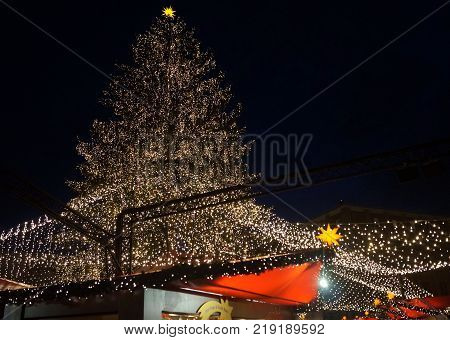 Cologne, Germany - December 16, 2017: Christmas Tree Lights up Christmas Market at Night. A huge Christmas tree with lights above the vendor pavilions at the Cologne Cathedral Christmas market.