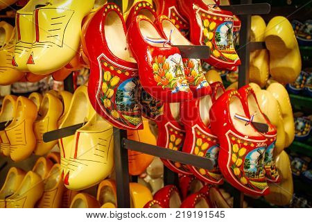 Dutch wooden shoes in the souvenir shop. Red and yellow Clog and Klomp in the storefront. Wooden klompen. poster