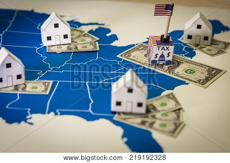 Family houses with dollar bills and central goverment tax over a US map.USA finance and economy concept related to the Tax Cuts and Jobs Act. approved by the Senate in December