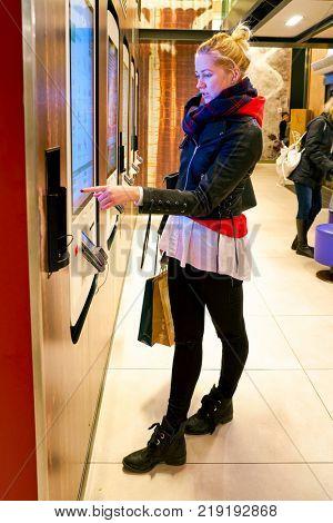 MILAN, ITALY - CIRCA NOVEMBER, 2017: customer at a McDonald's store place orders and pay through self ordering kiosk.