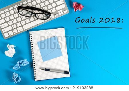 Top view 2018 goals list with keyboard, office supplies on blue desk. Targets, goal, dreams and New Year's promises for the next year.