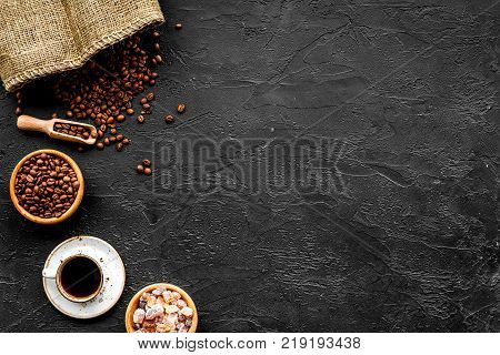 Coffee concept. Roasted beans, cup of espresso and sugar on black background top view.