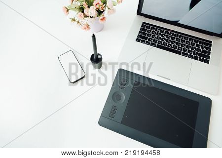Workspace of professional retoucher. laptop, pot of flower, stylus and tablet for retouching. Workspace of professional retoucher.