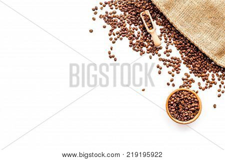 Fresh roasted coffee beans in bowl and scoop near canvas on white background top view.