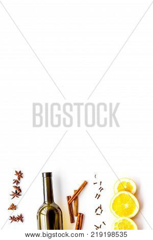 Ingredients for mulled wine. Wine in bottle, spices cinnamon and badian, citrus fruits on white background top view.