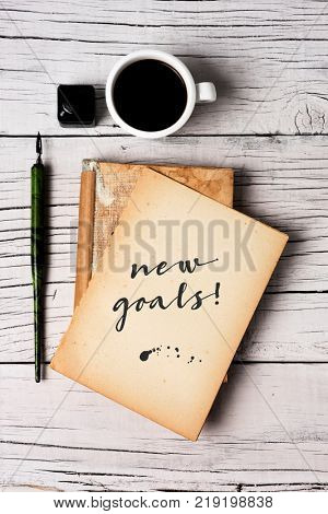 high angle view of a yellowish notepad with the text new goal written in it, a nib pen, a bottle of writing ink and a cup of coffee on a rustic white wooden table