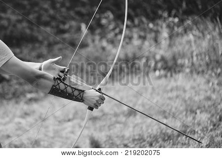 Archer hands with bow shoot arrow with blue and yellow fletchings on natural background