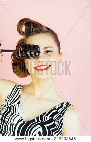 Music look and retro style pinup. Beauty and vintage fashion. Girl in glasses sing in microphone. Woman singer with stylish retro hair and makeup. Pin up young girl on pink background radio.