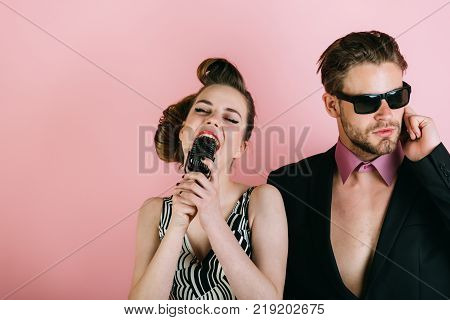 Music and love security. Pinup girl and man on pink radio. Beauty vintage fashion music band. Singer man and woman with retro hair and makeup. Couple in love in glasses sing in microphone. poster
