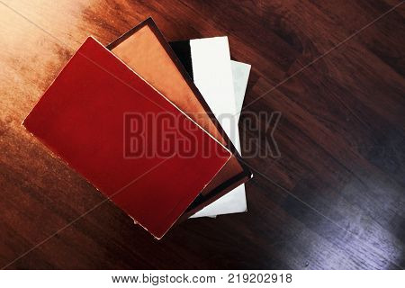 one book ontop of another book stacked ontop of each other against a wooden background