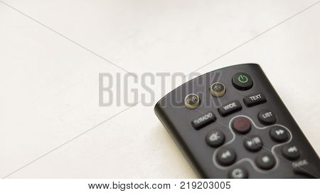 a TV remote control on a white background