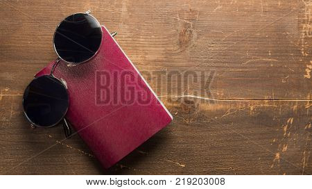 blank passport with black pair of glasses on a wooden background