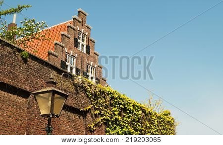 Netherlands in the city of Leiden in the Nieuwsteeg a traditional old Dutch house with a Dutch rooftop with blue sky background and a wall covered in vines with a streetlamp in front