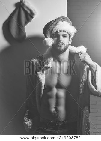 Handsome sexy christmas or xmas man with beard or new year muscular macho athlete bodybuilder in red santa claus coat and hat with bare torso six packs and abs on white grey background