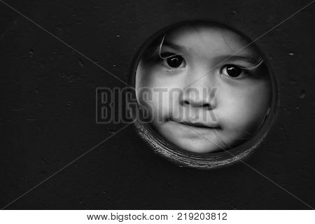 Cute baby boy with brown eyes looks through round hole in red wall at playground on wooden background copy space