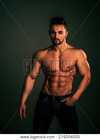 Athletic bodybuilder man on black background. Coach sportsman with bare chest in jeans. Sport and workout. Dieting and fitness. Man with muscular body and torso.
