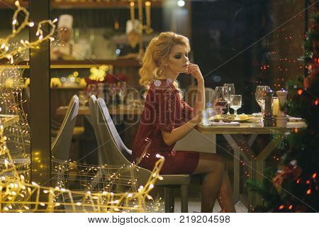 Winter holidays celebration concept. Girl enjoy party food drinks in restaurant. Festive fashion style decorations. xmas toast alcohol cheers. Woman in red dress celebrate new year and christmas.