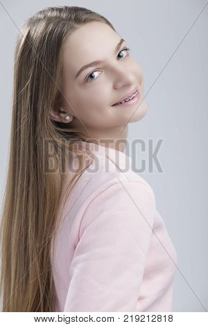 Dental Concepts. Portrait of Happy Teenage Female With Teeth Brackets. Posing Half Turned with Smile Against White.