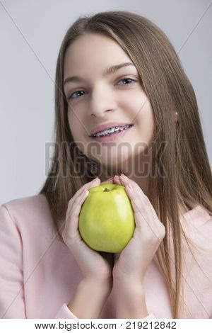 Dental Concepts. Portrait of Happy Teenage Female With Teeth Brackets. Posing With Green Apple and Smiling Against White.Vertical Image Orientation