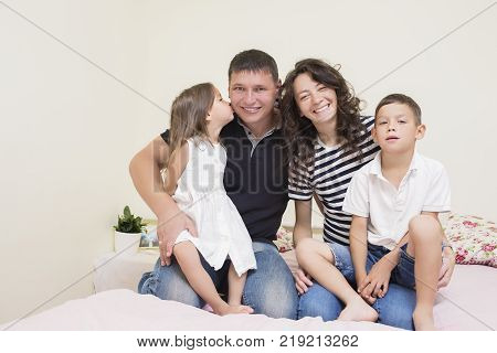 Family Ideas. Happy caucasian Family of Two Parent and Two Kids Sitting Together Embraced and Smiling Happily. Girl Kissing Her Father. Horizontal Image
