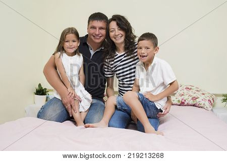 Portrait of Happy Caucasian Family with Two Kids Posing Together Embraced and Smiling Happily. Horizontal Image Orientation