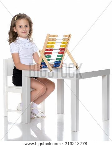 The girl counts on abacus.The concept of happiness, people, family, child, childhood, teaching math at school or kindergarten. Isolated on white background