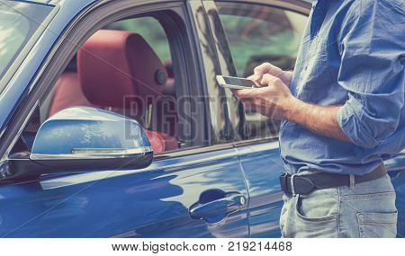Mobile phone apps for car owners concept. Man using smart phone to check status control his new car