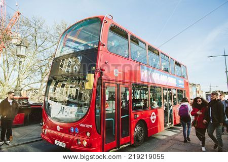 LONDON UNITED KINGDOM - MAR 10 2017: Red Double-decker bus on the London streets arriving in bus-station with lots of people inside ant outside - Notting Hill