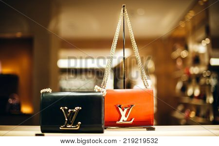 PARIS FRANCE - DEC 23 2017: Luxury Louis Vuitton handbag made from exclusive leather on sale during winter Christmas holidays in Paris France and golden LV logo