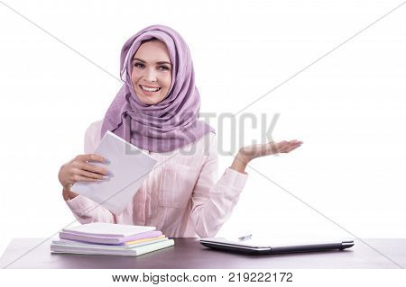 portrait of beautiful college student wearing hijab studying while presenting copy space isolated on white background