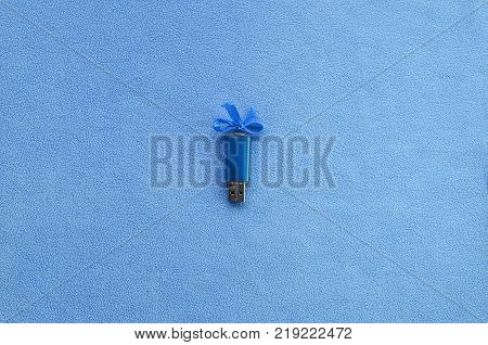 Brilliant blue usb flash memory card with a blue bow lies on a blanket of soft and furry light blue fleece fabric. Classic female gift design for a memory card