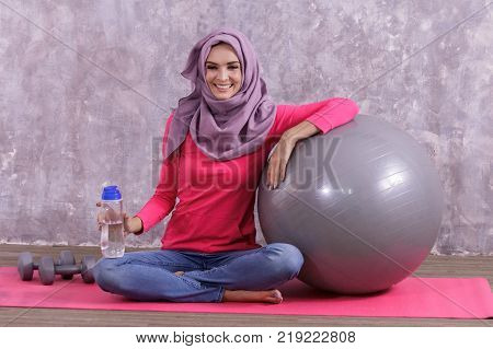 portrait of beautiful healthy woman wearing hijab sitiing on yoga mat with dumbbell and yoga ball with concrete wall on the background