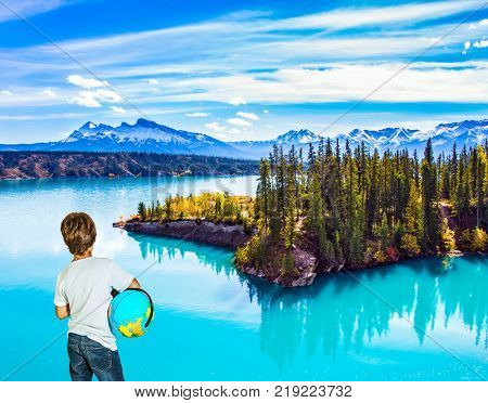 Exquisite Abraham Lake with turquoise water. Nine-year-old boy in jeans with a globe in his hands admires the lake. Concept of ecological and active tourism