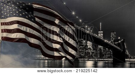 American flag flying the a Skyline Panoramic view new york city manhattan downtown skyline at night with skyscrapers and brooklyn bridge