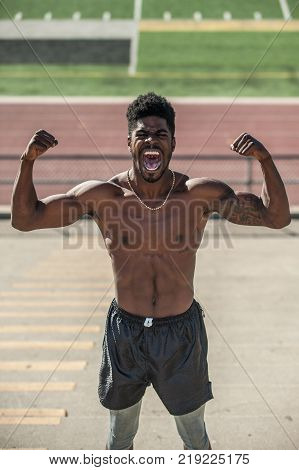 Muscular Jamaican athlete performing double bicep pose with primal scream on concrete bleachers at stadium in close view.