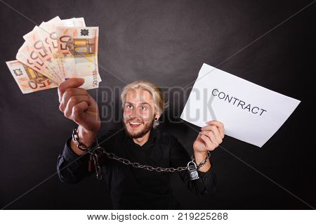 Stress at work no freedom pursuit of money concept. Mad man with chained hands holding money and contract studio shot on dark grunge background