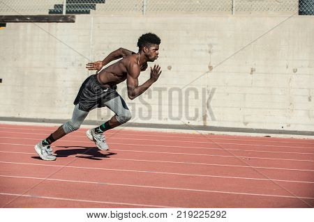 Muscular Jamaican athlete leaning forward for momentum while sprinting at stadium.