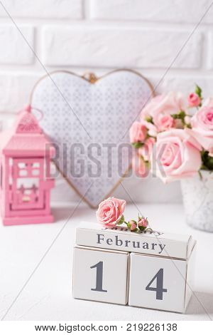 St. Valentine Day background. Calendar tender pink roses flowers decorative heart and pink lantern against white brick wall. Floral still life. Selective focus.