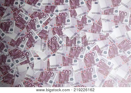 Close up background photo Amount of Five hundred notes of European Union Currency. Many pink 500 euro banknotes are adjacent. Symbolic texture photo for wealth