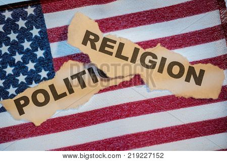 Old torn paper with the words Religion on top of the word Politics with American Flag