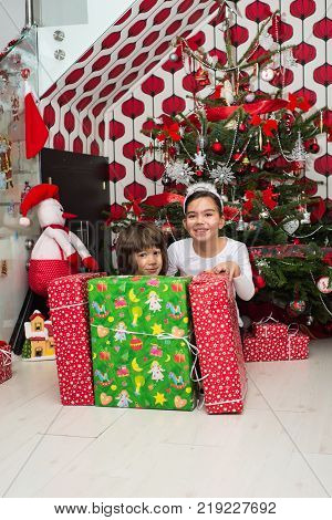 Happy Two Kids Behind Christmas Boxes In Their Home Having Fun