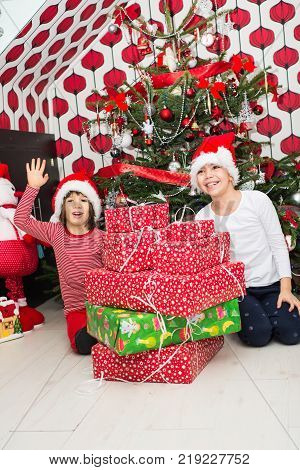 Cheerful Happy Kids With Many Christmas Gifts In Their Home