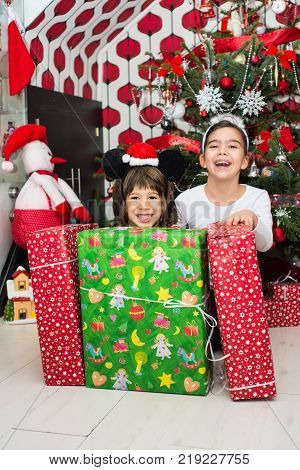 Laughing Kids With Christmas Gifts In Front Of Tree In Their Home