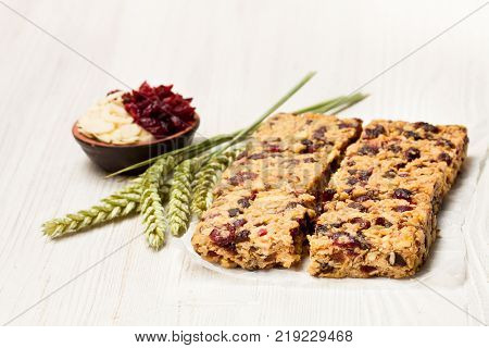 Healthy protein granola bars with dried berries and nuts on white wooden background